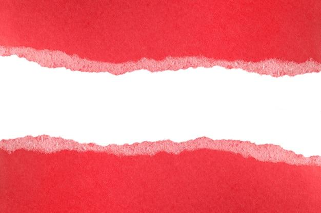 Zgrane kawałki czerwonego papieru na białym tle na białej przestrzeni. poszarpana krawędź kawałka papieru.