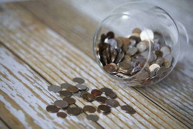 Zgromadzone monety ułożone w szklanych słoikach na podłodze