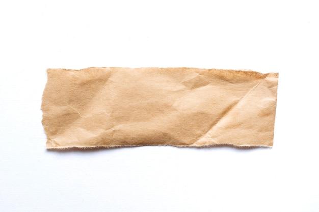 Zgrywanie kawałka brązowego papieru na białym tle