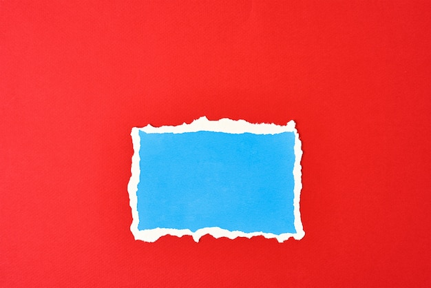 Zgrywanie niebieski papier z podartymi krawędziami na białym tle na czerwono