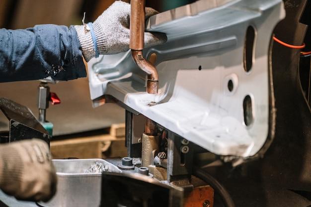 Zgrzewarka punktowa przemysłowa część samochodowa w fabryce. operator pracujący w przemyśle.