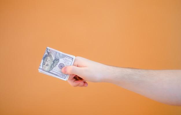 Ð¡zgubiona ręka daje pakiet dolarów na pomarańczowym tle
