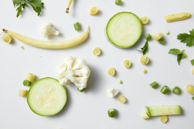Zhuchini, kalafior i fasola na białym stole. świeże ekologiczne zielone warzywa