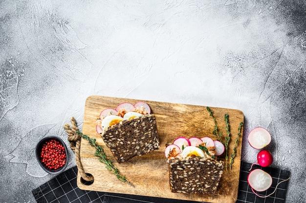 Ziarna chleba z wędzonym na gorąco łososiem, jajkami i rzodkiewką. zdrowa, zrównoważona żywność. szare tło, widok z góry, miejsca na tekst