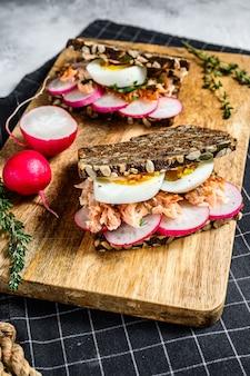 Ziarna chleba z wędzonym na gorąco łososiem, jajkami i rzodkiewką. zdrowa, zrównoważona żywność. szare tło, widok z góry.