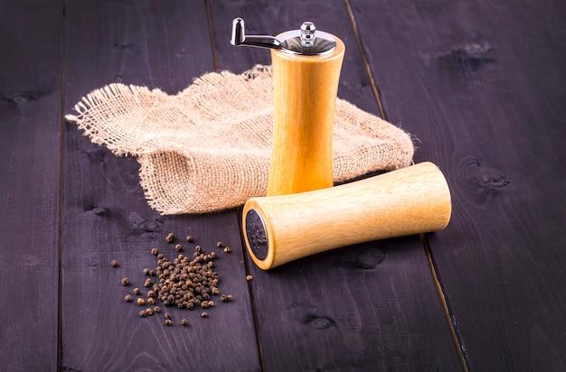 Ziarna czarnego pieprzu i czarny pieprz w proszku na drewnianym stole