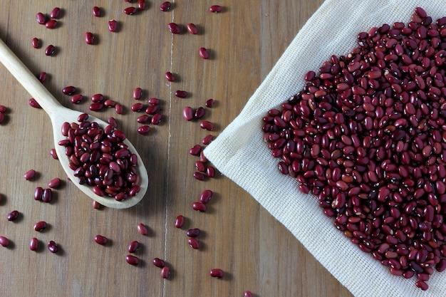 Ziarna czerwonej fasoli torba na stronie drewniany stół, drewniana łyżka z czerwonymi fasolami, odgórny widok