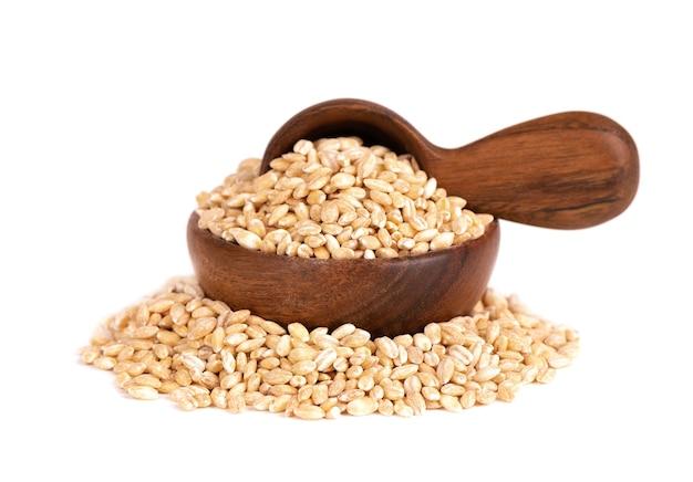 Ziarna jęczmienia perłowego w drewnianej misce i łyżce, na białym tle. nasiona jęczmienia z bliska.
