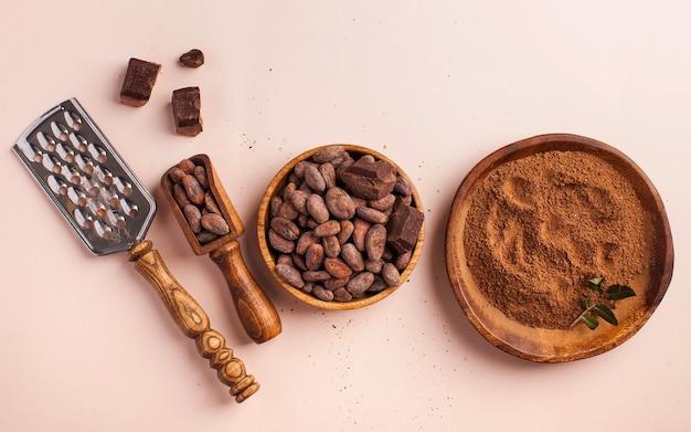 Ziarna kakaowe, kakao w proszku, surowa czekolada na różowej powierzchni