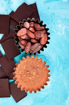 Ziarna kakaowe na niebieskim stole. kawałki ciemnej czekolady