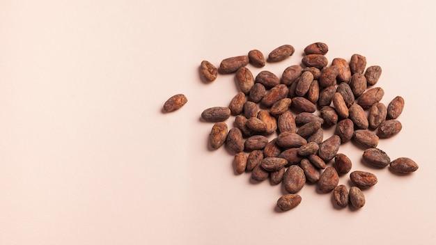 Ziarna kakaowe na różowej powierzchni