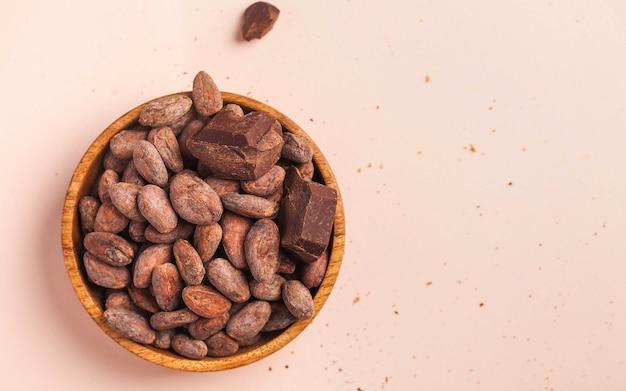 Ziarna Kakaowe W Drewnianej Misce Na Różowej Powierzchni Premium Zdjęcia