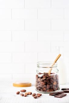 Ziarna kakaowe w szklanym słoju na jasnym stole kuchennym. kulinarne jedzenie gotowanie tło do robienia tradycyjnej czekolady. selektywne skupienie.