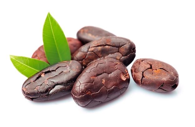 Ziarna kakaowe z liśćmi z bliska na białym tle