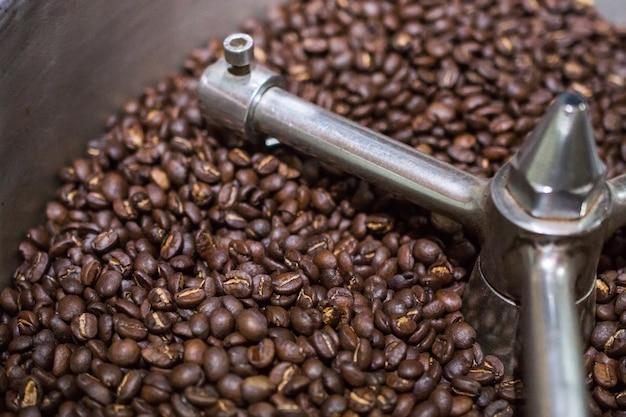 Ziarna kawy arabica w procesie prażenia ekspresu do kawy. palone ziarna kawy w profesjonalnym automacie z obracającą się chłodnicą