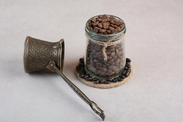 Ziarna kawy i cezve na białej powierzchni