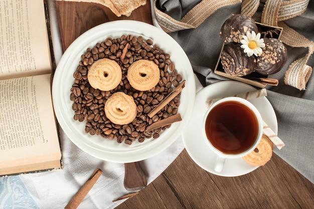 Ziarna kawy i ciastka na spodku z filiżanką herbaty