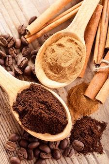 Ziarna kawy i cynamon mielony zbliżenie w drewniane łyżki