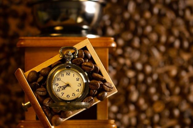 Ziarna kawy i kieszeń obserwują tacę młynka ręcznego na stole. widok z góry i miejsce. poranna kawa.