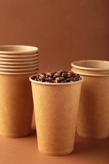 Ziarna kawy i papierowa filiżanka na brązowym tle. widok z góry.
