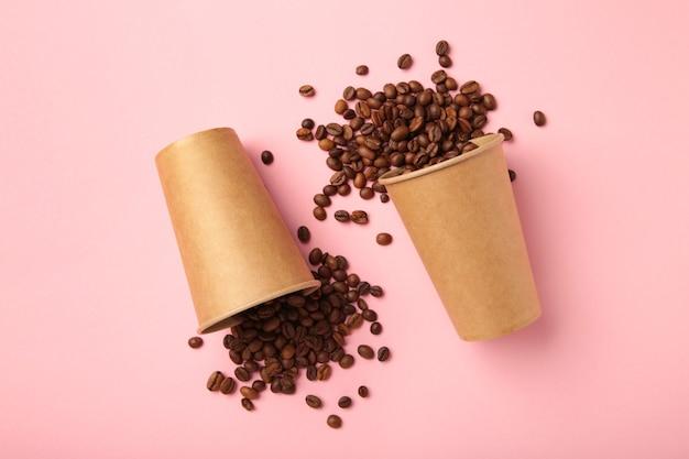 Ziarna kawy i papierowe kubki do kawy na różowym tle.