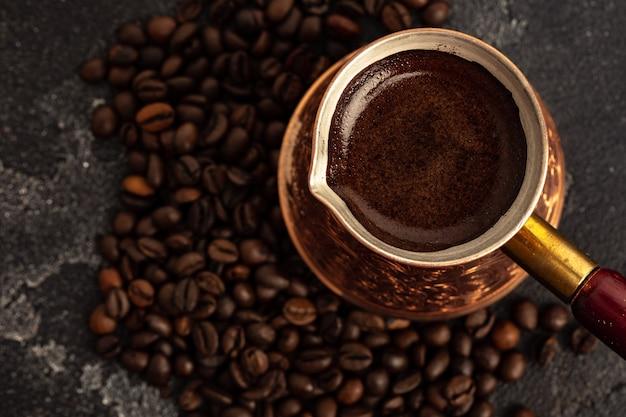 Ziarna kawy i turk na ciemnej powierzchni