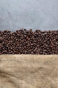 Ziarna kawy i worek na starym tle cementu