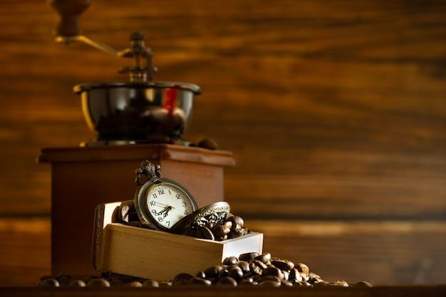 Ziarna kawy i zegarek kieszonkowy. ręczny młynek na stole w godzinach porannych. czas na kawę.