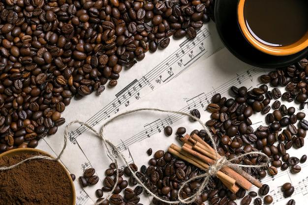 Ziarna kawy, kawa mielona i filiżanka kawy parzonej na tle nuty, widok z góry z miejsca na tekst. martwa natura. makieta. płaskie ułożenie