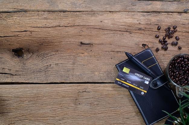 Ziarna kawy książki karty kredytowej umieszczone na tle widoku z góry tabeli