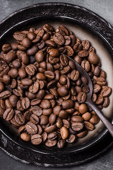 Ziarna kawy leżące płasko z łyżeczką