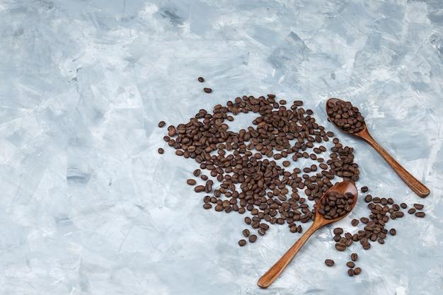 Ziarna kawy leżał płasko w drewniane łyżki na tle szarego tynku. poziomy