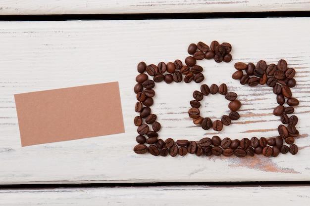 Ziarna kawy na białym stole w kształcie aparatu fotograficznego. pusty beżowy papier na lato.
