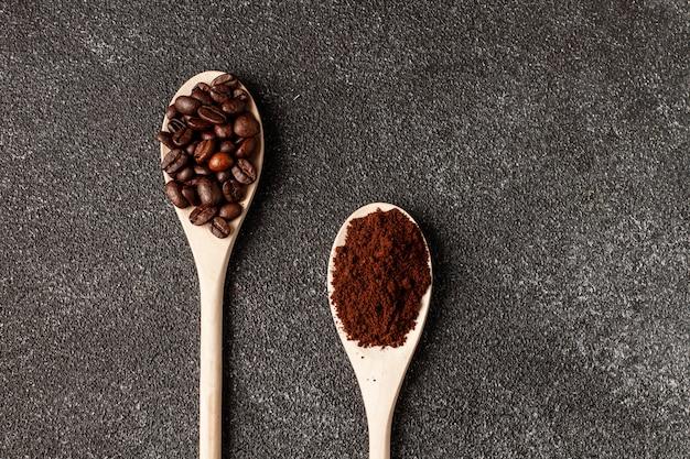 Ziarna kawy na drewnianą łyżką. ciemny beton.