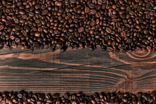 Ziarna kawy na drewnianym tle. widok z góry. martwa natura. skopiuj miejsce. leżał płasko.
