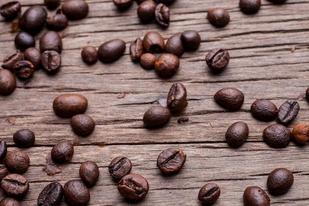 Ziarna kawy na starej drewnianej podłodze tle.