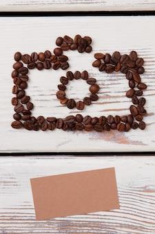 Ziarna kawy na stole tworząc aparat fotograficzny. pusty beżowy papier. białe drewniane deski na powierzchni.