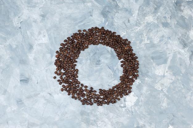 Ziarna kawy na szarym tle tynku. leżał płasko.