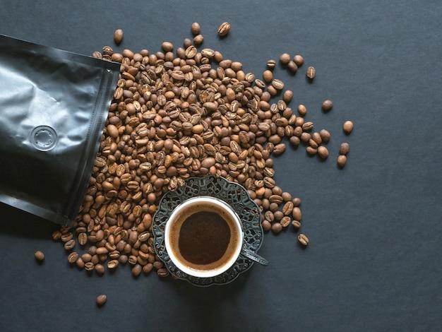 Ziarna kawy rozlane z opakowania na czarnym stole.