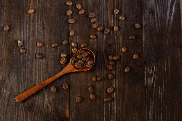 Ziarna kawy rozrzucone na ciemnym tle drewniane drewnianą łyżką