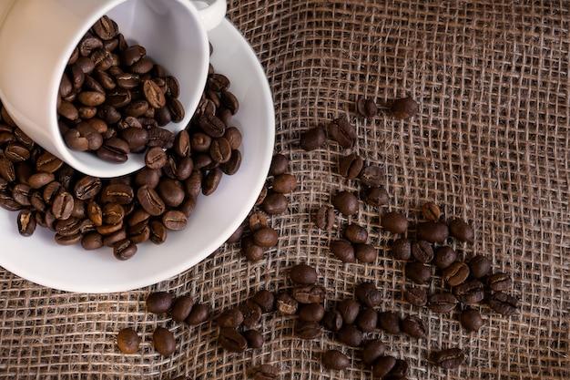 Ziarna kawy rozsypane z porcelanowego białego kubka na płótnie