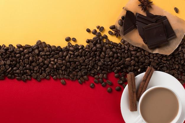 Ziarna kawy są rozrzucone na czerwonym i żółtym papierze i białej filiżance, cynamonie, anyżu gwiazdkowatym, czekoladzie, komercyjnym copyspace.