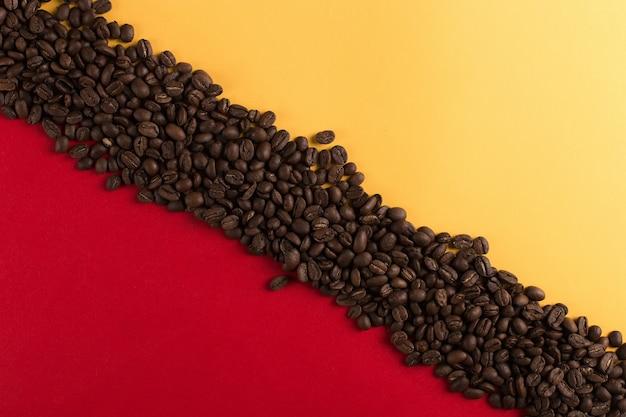 Ziarna kawy są rozrzucone na czerwonym i żółtym papierze, komercyjnym copyspace.