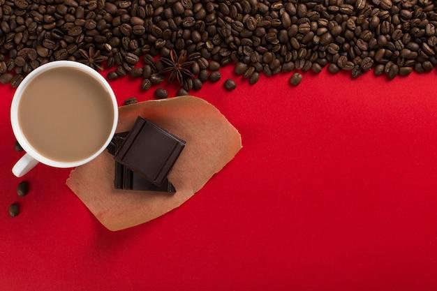 Ziarna kawy są rozrzucone na czerwonym papierze i białej filiżance, czekoladzie, komercyjnym copyspace.