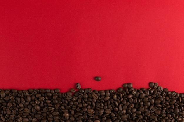 Ziarna kawy są rozrzucone na czerwonym papierze z bliska, komercyjne copyspace.