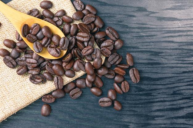 Ziarna kawy są rozrzucone w drewnianych łyżkach i na workach na drewnianym stole