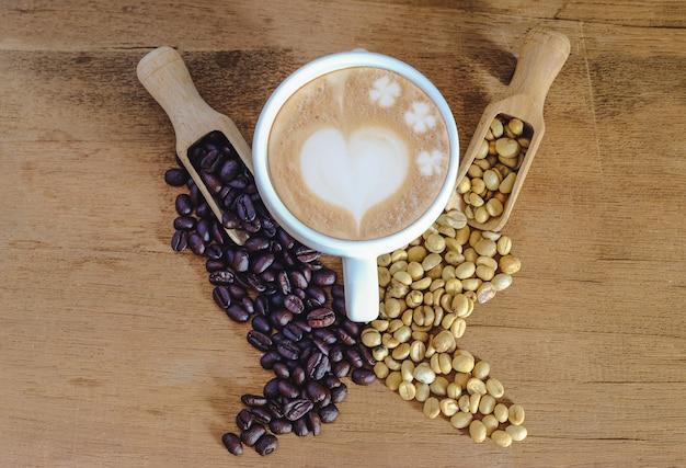 Ziarna kawy surowej i ziarna kawy ziarnistej w drewnianej łyżce i gorącej późnej sztuce ok