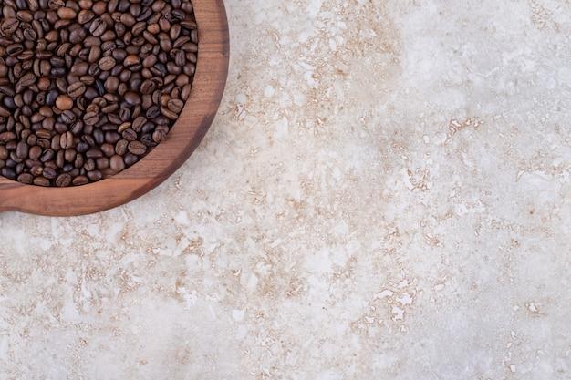 Ziarna kawy ułożone w stos na drewnianej tacy
