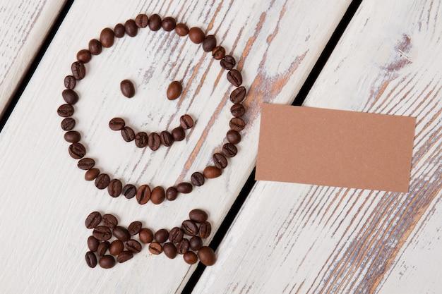Ziarna kawy ułożone w szczęśliwą buźkę z muszką. pusty beżowy papier na lato. białe drewniane deski na powierzchni.
