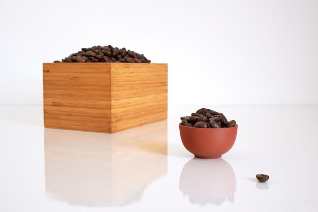 Ziarna kawy w bambusowym pudełku i gliniany kubek z ziaren kawy na białym lubi